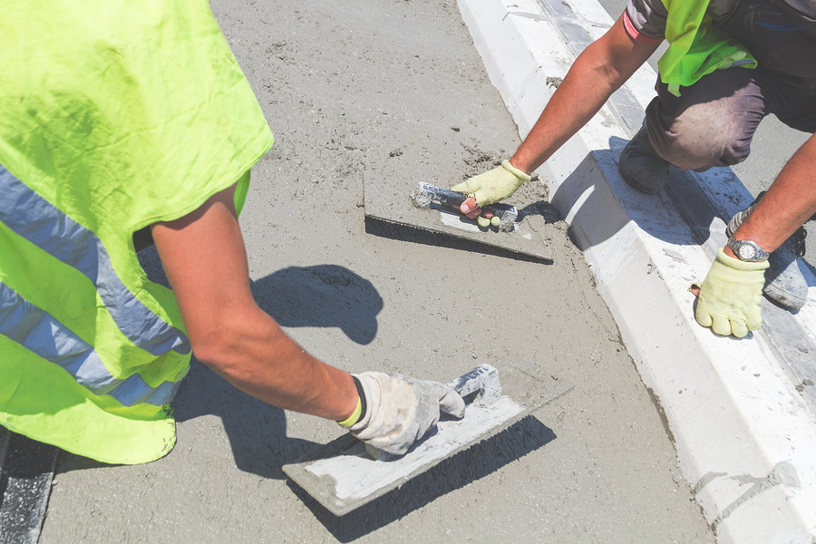 two workers scraping the cement